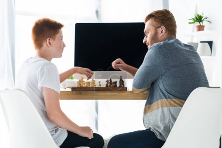 side view of father and son playing chess at home