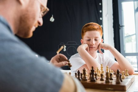 pensive son looking at chessboard at home