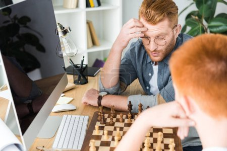 pensive red hair father and son playing chess at home