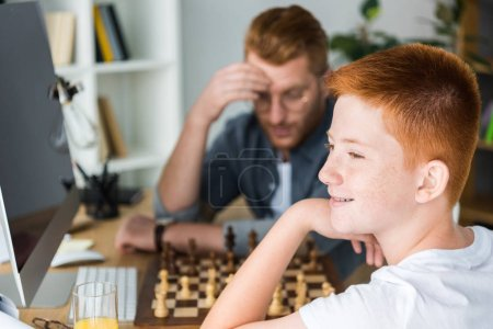 pensive father and son playing chess at home