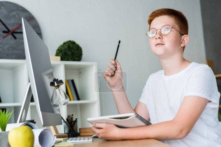 Photo for Pensive preteen ginger hair boy holding pen and notebook at home - Royalty Free Image