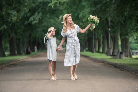 mother and daughter in straw hats with bouquet holding hands and walking on path in green park