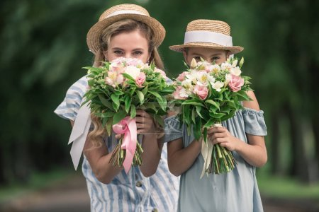 happy mother and daughter in straw hats posing with flower bouquets in front of the faces