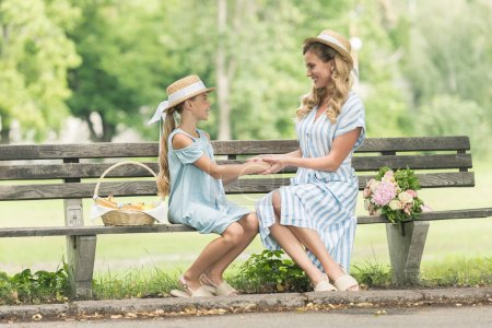 attractive mother and cheerful daughter in straw hats holding hands and sitting on bench in park