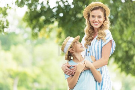 beautiful smiling mother and daughter in straw hats