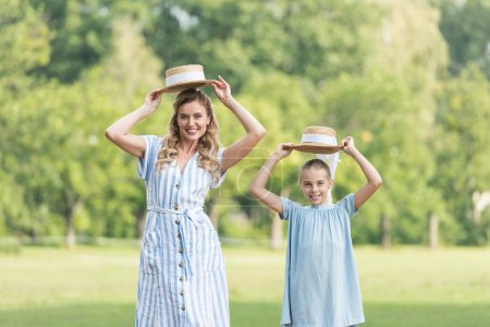 Photo for Happy mother and adorable daughter posing with straw hats on green lawn - Royalty Free Image