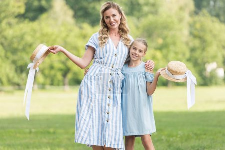 Photo for Cheerful mother and daughter posing with straw hats together - Royalty Free Image