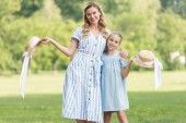 cheerful mother and daughter posing with straw hats together