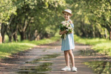 beautiful preteen child in straw hat with bouquet of flowers posing in garden
