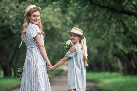 mother and daughter in straw hats holding hands and walking in green park