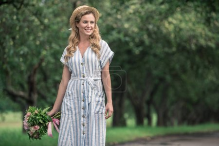 beautiful stylish woman in dress and straw hat with bouquet standing on path in park