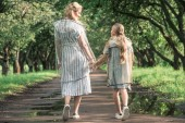 back view of mother and daughter holding hands and walking in transparent raincoats on wet road
