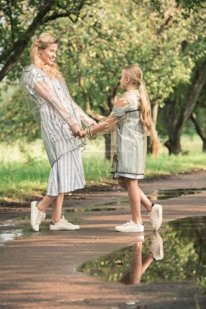 attractive mother and blonde daughter in transparent raincoats holding hands on wet road in park