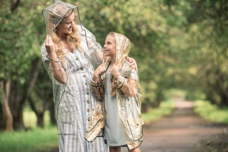 beautiful mother and daughter in transparent raincoats in park