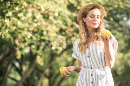 happy blonde woman in straw hat posing with two apples in hands