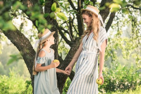 beautiful mother and happy daughter in straw hats with appples looking at each other