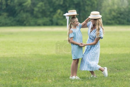 stylish mother and daughter holding straw hats over heads of each other