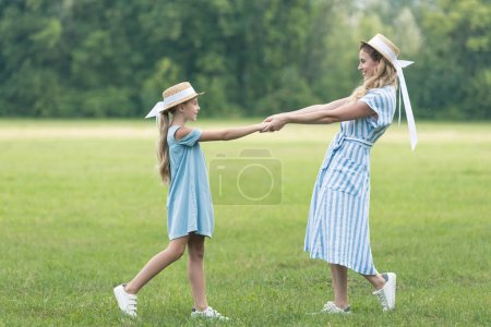 happy mother and adorable daughter holding hands and twisting on green lawn
