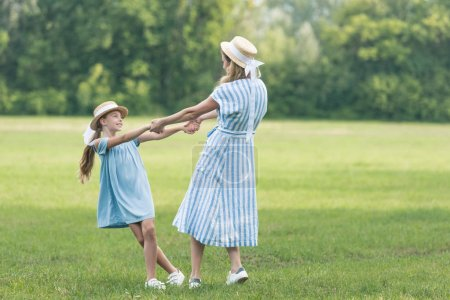 mother and daughter holding hands, twisting and having fun on green lawn