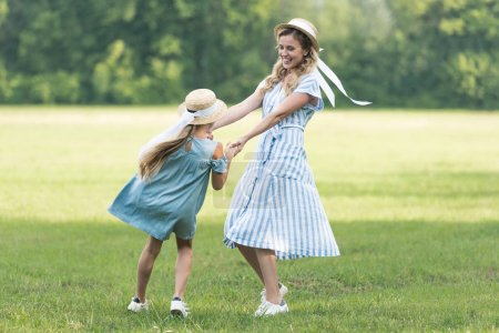 beautiful mother and daughter holding hands, twisting and having fun on green grass