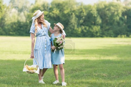 beautiful mother and daughter with wicker basket and bouquet walking on green lawn