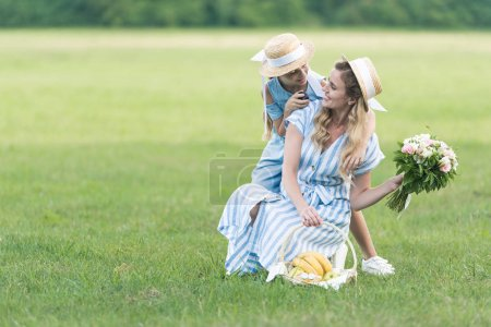 happy parent and daughter having picnic with fruits and flower bouquet on green lawn