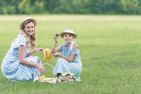 smiling mom and daughter having picnic with fruits and bouquet on green lawn