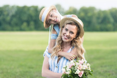 smiling mother and daughter posing in straw hats with bouquet of flowers