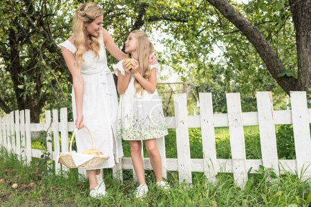 blonde mother and daughter with fruits in wicker basket posing near white fence in garden
