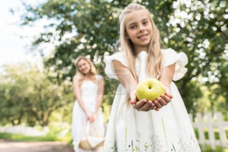 preteen daughter holding apple, young mother with wicker basket on background, selective focus