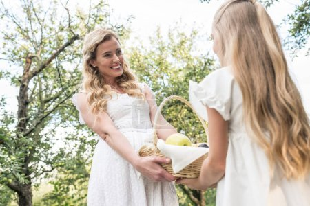beautiful blonde mother and daughter holding wicker basket with fruits in orchard