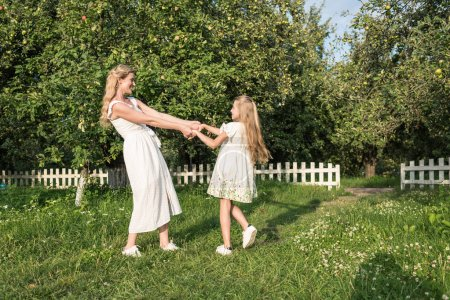 beautiful happy mother and daughter holding hands and twisting in garden with white fence