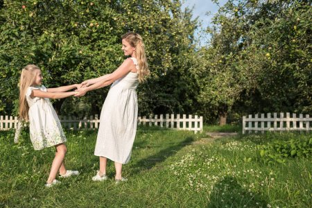 attractive mother and daughter in white dresses holding hands and twisting in orchard