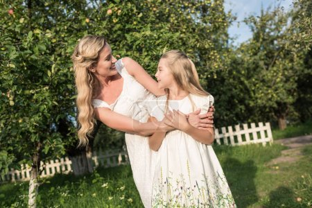 Photo for Mother and smiling daughter in white dresses embracing in rural garden - Royalty Free Image