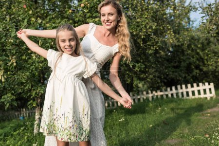 attractive mother and adorable daughter in white dresses holding hands in garden