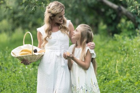 adorable daughter and mother holding wicker basket with fruits
