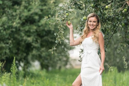 cheerful attractive woman in white dress posing in apple orchard