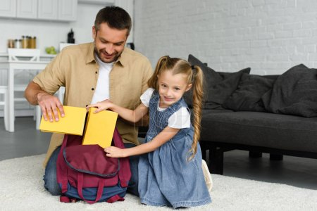 smiling father helping little daughter packing backpack for first day at school, back to school concept