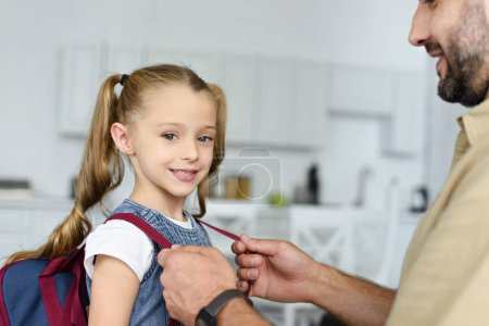 partial view of father helping daughter to wear backpack at home, back to school concept