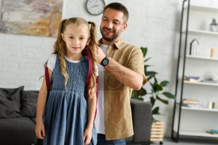 portrait of father helping daughter to wear backpack at home, back to school concept