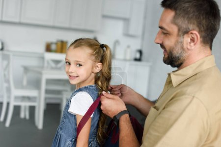 side view of father helping daughter to wear backpack at home, back to school concept