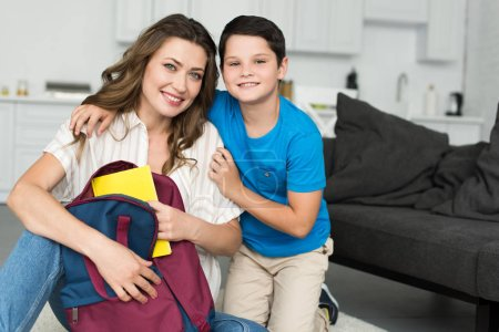 portrait of smiling boy hugging mother with book and backpack at home, back to school concept