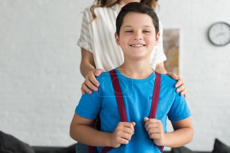 partial view of mother and smiling boy with backpack at home, back to school concept