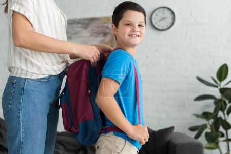 partial view of mother helping smiling son to wear backpack at home, back to school concept