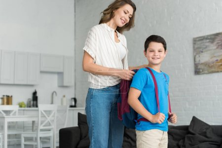 smiling mother helping son to wear backpack at home, back to school concept