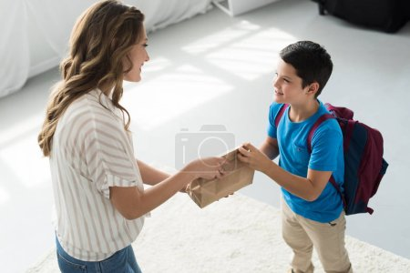 Photo for Side view of mother giving paper package with meal to son with backpack at home, back to school concept - Royalty Free Image