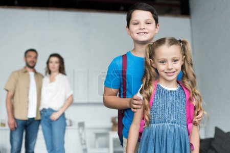 selective focus of smiling siblings with backpacks and parents behind, back to school concept