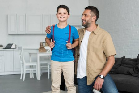 smiling father and son with backpack at home, back to school concept