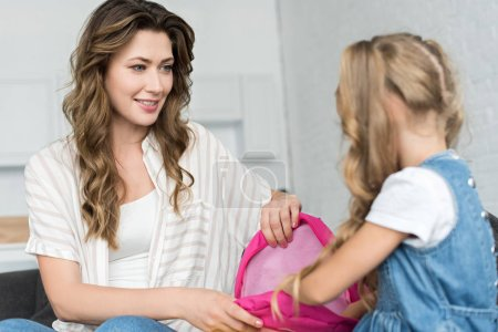 Photo for Mother and daughter packing backpack to school together at home - Royalty Free Image