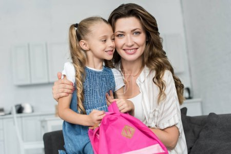 portrait of smiling mother and little daughter with pink backpack on sofa at home